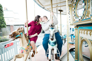 engagement photo kissing on carousel