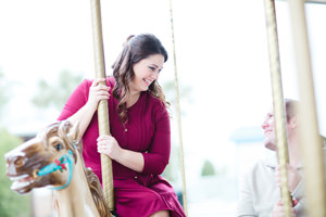 engagement photo looking at each other on carousel