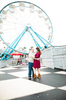 engagement photo hugging with ferris wheel in background