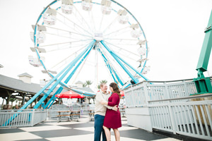 engagement photo hugging and looking at each other with ferris wheel in background