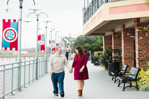 engagement photo walking along the boardwalk