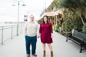 engagement photo holding hands on boardwalk