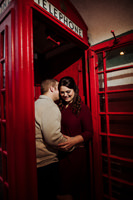engagement photo whispering in ear in phone booth